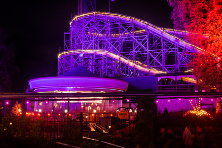 Helsinki, Finland - 19 October 2019: The Carnival of Light event at the Linnanmaki amusement park. Rides Karuselli and roller coaster Vuoristorata in motion. Night illumination, long exposure.