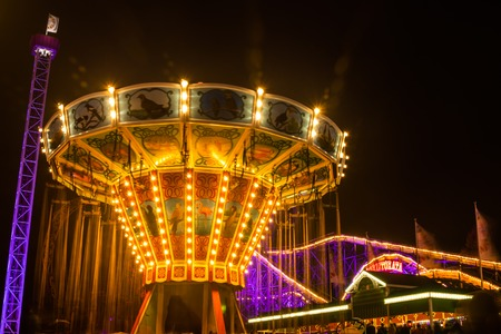 Helsinki, Finland - 19 October 2019: The Carnival of Light event at the Linnanmaki amusement park. Ride chain carousel Ketjukaruselli in night illumination.