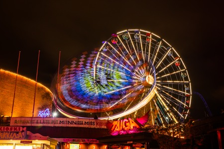 Helsinki, Finland - 19 October 2019: The Carnival of Light event at the Linnanmaki amusement park. Ride Ferris Wheel Rinkeli and Kehra in motion, night illumination, long exposure.