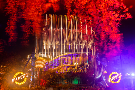 Helsinki, Finland - 19 October 2019: The Carnival of Light at the Linnanmaki amusement park. Rides Kieputin, Ketjukaruselli and Vuoristorata in motion. Night illumination, long exposure. Sajtókép