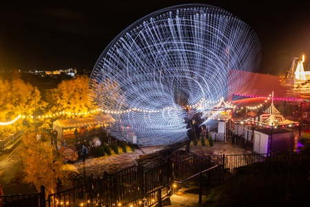 Helsinki, Finland - 19 October 2019: The Carnival of Light event at the Linnanmaki amusement park. Ride Magia in motion, night illumination. Long exposure.