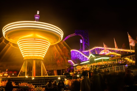 Helsinki, Finland - 19 October 2019: The Carnival of Light event at the Linnanmaki amusement park. Ride chain carousel Ketjukaruselli in motion. Night illumination, long exposure.