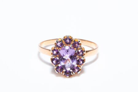 Beautiful golden ring with purple gemstone isolated on white background