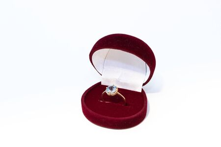 Golden ring with blue gemstone in a red jewelry box on white background