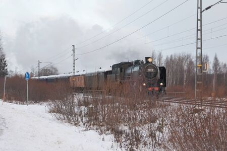 KOUVOLA, FINLAND - DECEMBER 26, 2018: Steam train Ukko-Pekka going from Kouvola to Kotka. The steam locomotive Hr1 1009 was made in 1948 and restored in 1993.