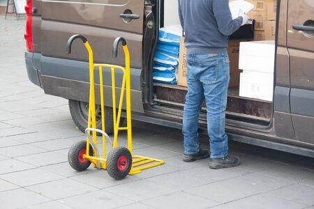 Le chauffeur-livreur décharge une camionnette avec des marchandises dans un camion.