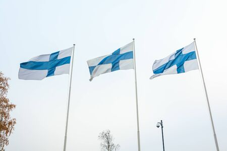 Three national flags of Finland on poles at wind and sky background.