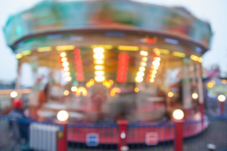 A blurry colorful carousel in motion at the amusement park, evening illumination. The effect of bokeh and long exposure 写真素材