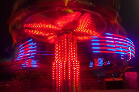 A blurry colorful carousel in motion at the amusement park, night illumination. The effect of bokeh and long exposure Stock Photo