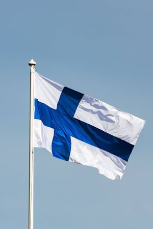 Finnish national flag on the wind against the blue sky Stock Photo