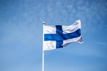 Finnish national flag on the wind against the blue sky Stockfoto