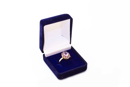 Golden ring with purple gemstone in a blue jewelry box on white background