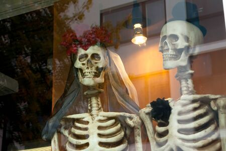Two dressed up for honeymooners skeletons on the window. Stock Photo