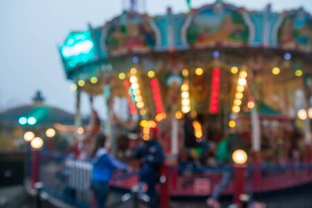 A blurry colorful carousel in the amusement park at evening illumination. The effect of bokeh.