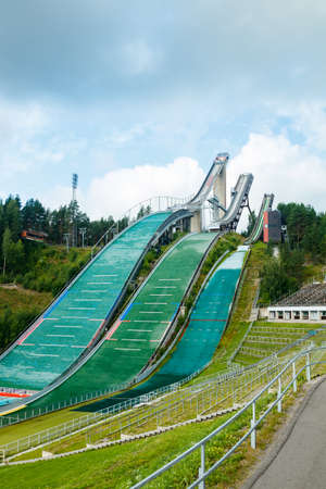 Lahti, Finland - 4 August 2020: Lahti sports center with three ski jump towers. Sportsman is jumping from the smallest ski jump tower.