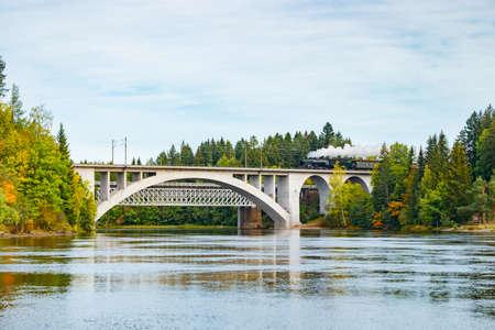 Kouvola, Finland - 18 September 2020: Autumn landscape of bridge with moving old steam passenger train Ukko-Pekka and Kymijoki river waters in Finland, Kouvola, Koria