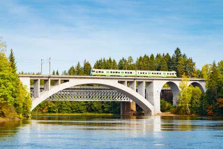 Autumn landscape of bridge with moving passenger train and Kymijoki river waters in Finland, Kouvola, Koria Stock fotó