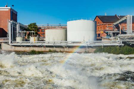Kouvola, Finland - 15 September 2020: Old red brick buildings of Upm factory on rapids Kuusankoski with rainbow