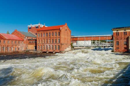 Kouvola, Finland - 15 September 2020: Old red brick buildings of Upm factory on rapids Kuusankoski. Sajtókép