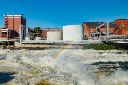 Kouvola, Finland - 15 September 2020: Old red brick buildings of Upm factory on rapids Kuusankoski with rainbow