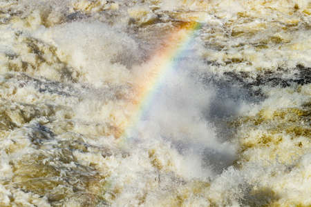 Splashing water waves with rainbow on the fast river