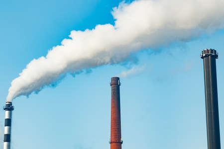 Chimney smoke at factory against blue sky Stockfoto