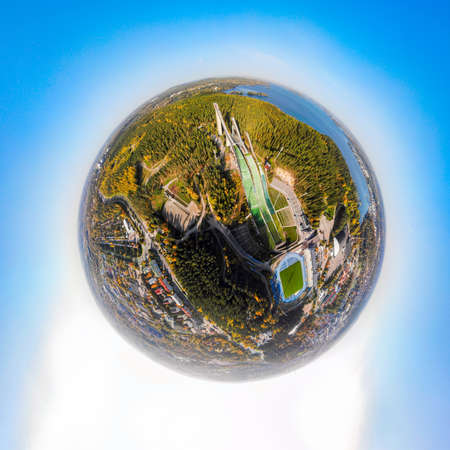 A three dimensional aerial panoramic view of Lahti sports center with three ski jump towers, in a mini planet panorama style. 免版税图像