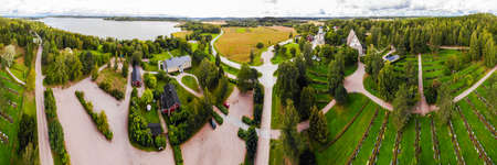 Panoramic aerial view of old medieval stone church of St. Mary and cemetery in Hollola, Finland
