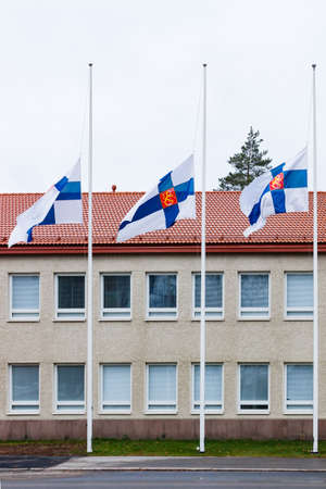 Three finnish flags lowered to half mast on the occasion of mourning at cloudy autumn day 新闻类图片