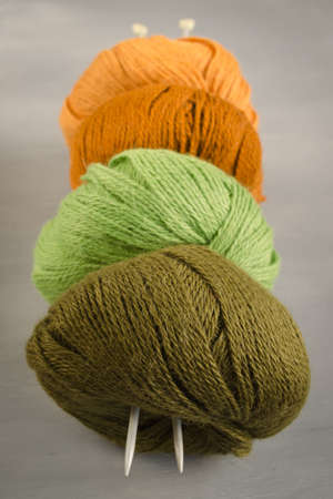 Orange, brown, green and marsh woolen yarn and knitting needles on a gray background Stock Photo