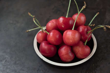 Fresh ripe cherries on a plate on a dark background. Copy space. Stock fotó