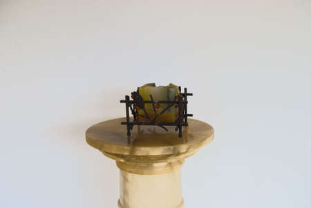 The metal candlestick with candle on the stone table