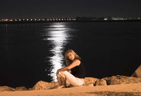 Blond woman sitting near river at the night photo