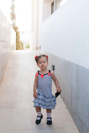 The beautiful caucasian  baby girl walking alone in street Stock Photo