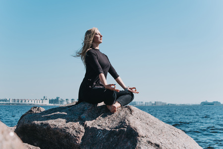 The girl meditates sitting on a rock on the sea in sunny weather with her eyes closed Stock fotó