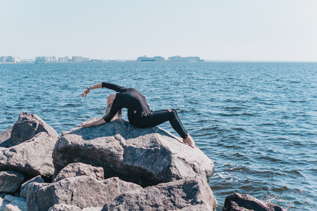 Flexible gymnast makes a deflection in the back on a stone on the sea