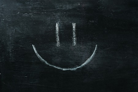 White happy smiley face on a blackboard background, closeup Stock fotó