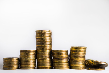A pile of gold coins, a different stack height. Collapse, decline, investment, finance, business. Isolated white background. Stock Photo