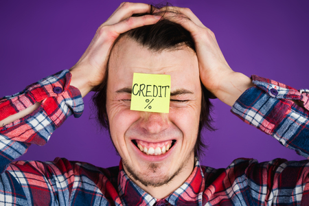 Caucasian man took a loan, grabs his head and cries, a close-up portrait. The man is shocked by the interest on the loan. Credit card sticker - purple background