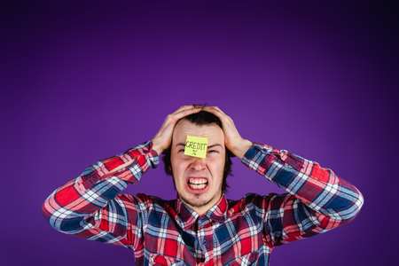 Caucasian man is angry with credit, grabs his head and cries, a close-up portrait. The man is shocked by the interest on the loan. Credit card sticker - purple background Stock Photo