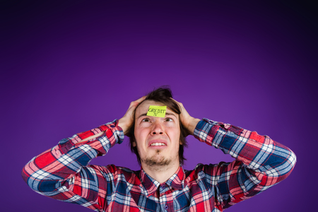 Caucasian man looks at a sticker with the inscription credit, grabs his head, close-up portrait. The man is shocked by the interest on the loan - the purple background Stock Photo