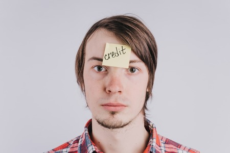 Sad man looks directly, the sticker is glued on the forehead with the word credit . A young guy is upset by debt, credit. Close-up portrait, isolated