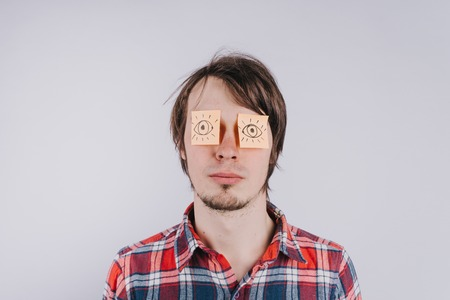 Stickers with painted eyes are glued on mans eyelids, isolated white background