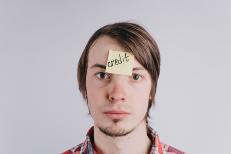 Sad man looks directly, a sticker on his forehead with the word credit. A young guy is upset by debt, credit. Close-up portrait, isolated