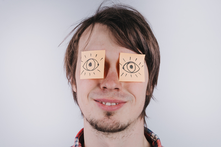Stickers with painted eyes are glued on mans eyelids, isolated white background, close-up Banque d'images - 99698064