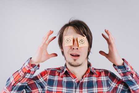 Stickers with painted eyes are glued to the eyes of a guy, a man comes insight, an isolated white background