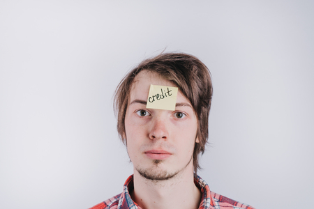 A man with sad eyes looks directly, a sticker on his forehead with the word credit. A young guy is upset by debt, credit. Close-up portrait, isolated Stock Photo