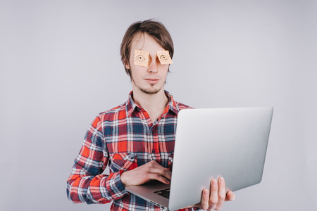 Man prints on a computer with his eyes closed, stickers with painted eyes are glued to the eyes of a guy, an isolated white background Banco de Imagens