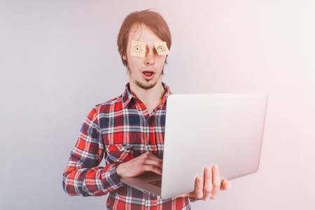 Man is surprised at what he sees on the Internet with his eyes closed, stickers with painted eyes are glued to the eyes of a guy, an isolated white background - toning
