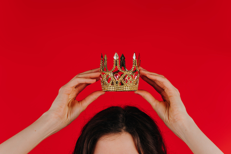 Gold crown on a red background in female hands over her head, the girl holds a toy crown over her head